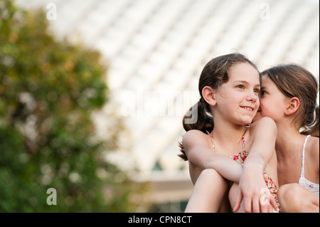 Girl telling secret to another girl - Stock Photo