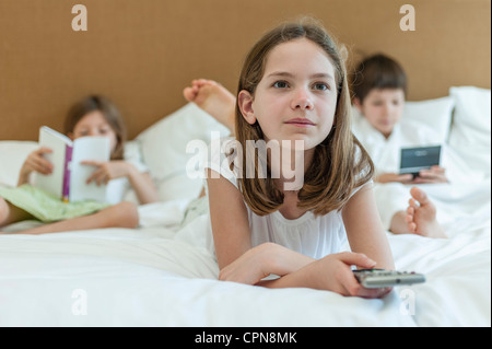Girl lying on bed watching TV, siblings in background - Stock Photo