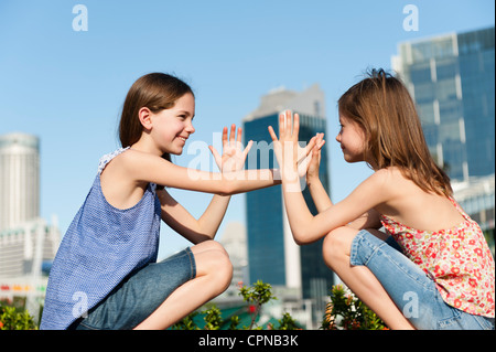 Girls playing pattycake - Stock Photo