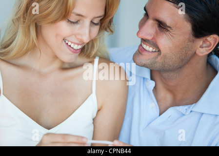 Couple looking at pregnancy test, smiling - Stock Photo
