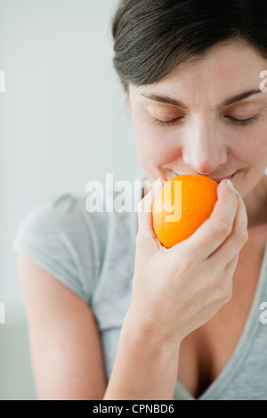 Woman smelling fresh orange - Stock Photo