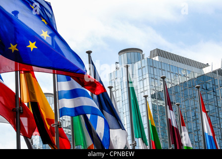 European Parliament in Brussels with flags on the foreground - Stock Photo