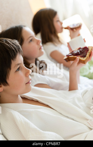 Siblings relaxing on bed, girls eating toasts in background - Stock Photo