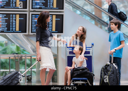 Family in airport with luggage - Stock Photo