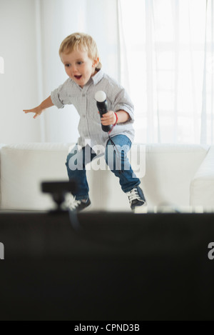 Little boy jumping on sofa with microphone in hand - Stock Photo