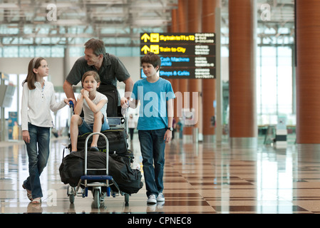Family pushing luggage cart in airport - Stock Photo