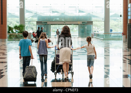 Family pushing luggage cart in airport, rear view - Stock Photo
