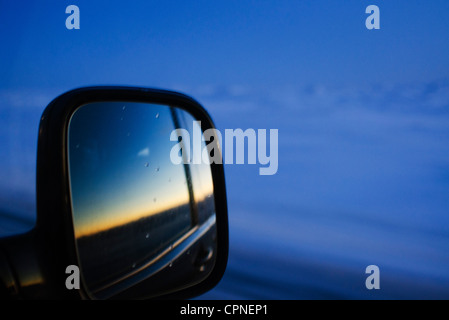 Sunset reflected in car side-view mirror - Stock Photo