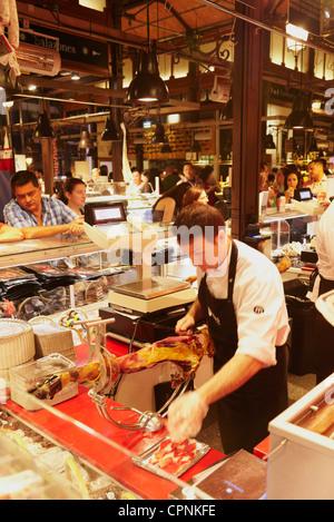 Butcher cutting cured iberian ham. Mercado de San Miguel. Madrid. Spain - Stock Photo