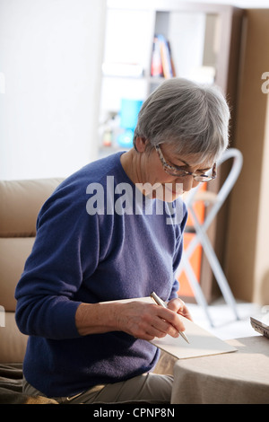 ELDERLY PERSON WRITING - Stock Photo