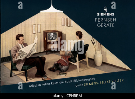 broadcast, television, viewers, family in living-room, father is reading the newspaper, advertising for Siemens - Stock Photo
