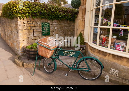 Old bike used as shop sign for Tisanes Tea Rooms, Broadway, Worcestershire, Cotswolds, UK - Stock Photo