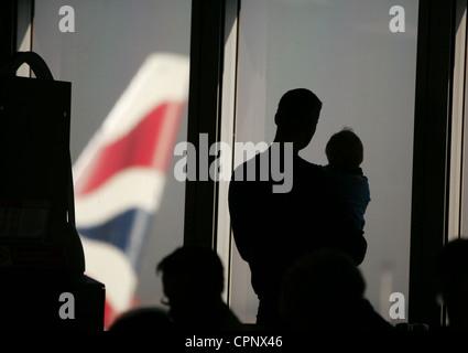 British Airways passengers at London Heathrow wait for flights - Stock Photo