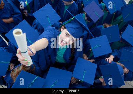 A child celebrates and exam pass in a fake degree honors ceremony at a junior school in Wythenshawe Manchester - Stock Photo