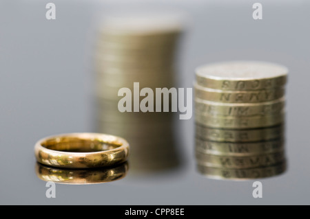 Money with wedding ring showing concepts of pre-nuptial agreement, breakup, divorce settlement, pensions or planning - Stock Photo