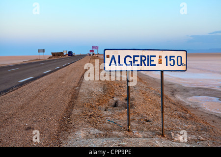 Road to the Algeria across a large endorheic salt lake Chott el Djerid  in early morning and inscription on plate, - Stock Photo