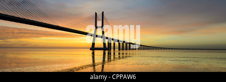Panoramic image of the Vasco da Gama bridge in Lisbon, Portugal during sunrise with reflection in the Tagus river - Stock Photo