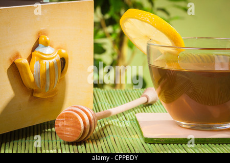 Honey dipper next to cup of tea - Stock Photo