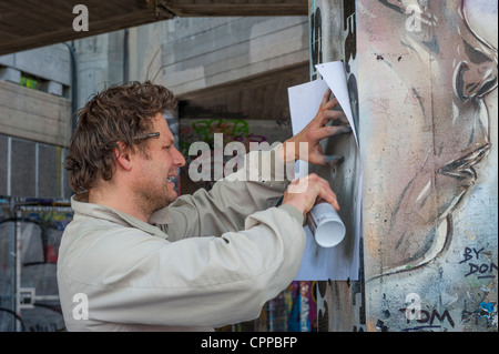London , Southbank , Riverside , Embankment , street artist Don spray can painting graffiti mural picture black - Stock Photo