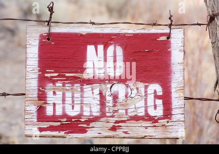 no hunting sign on a wooden board fastened to a barbed wire fence - Stock Photo