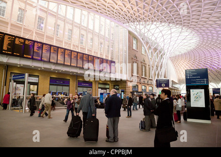People looking at the departure board on the concourse, Kings Cross station, London UK - Stock Photo