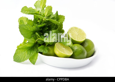Bowl with limes and a bunch of mint on white background - Stock Photo