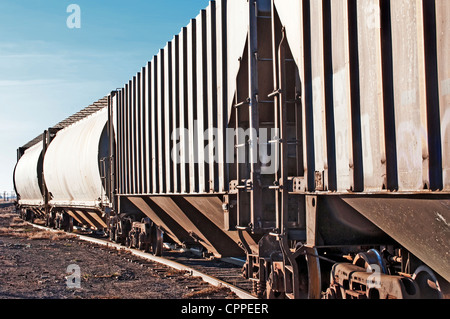 Empty railcars waiting on a siding to be loaded with grain from the local silo. - Stock Photo