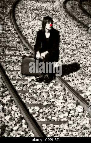 the sad clown on train tracks - Stock Photo