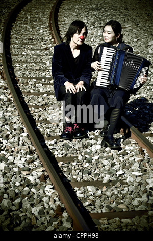 a clown couple sitting on railroad tracks, the woman plays music - Stock Photo