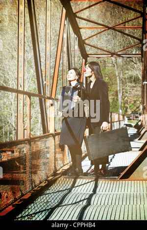 a couple of clowns standing on an old railway bridge, the woman playing music on an accordion - Stock Photo