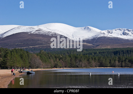 Loch Morlich in the Cairngorms region of Scotland on a calm and sunny spring day with snow covered Cairn Gorm  mountain - Stock Photo