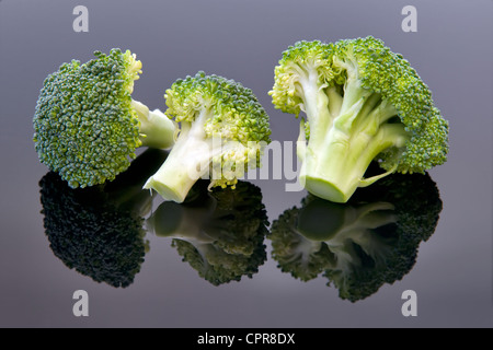 Studio image of fresh uncooked broccoli with reflection on black background - Stock Photo