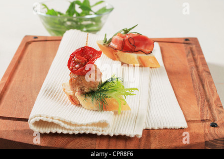 Meatball and prosciutto canapes on a cutting board - Stock Photo