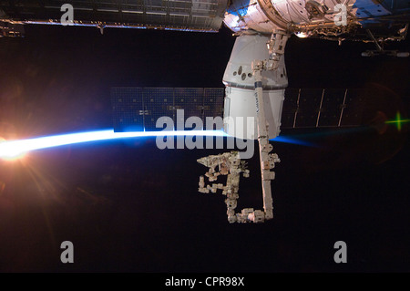 With rays of sunshine and the thin blue atmosphere of Earth serving as a backdrop the SpaceX Dragon commercial cargo - Stock Photo