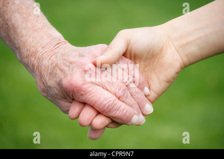 Senior lady and young woman holding hands - Stock Photo