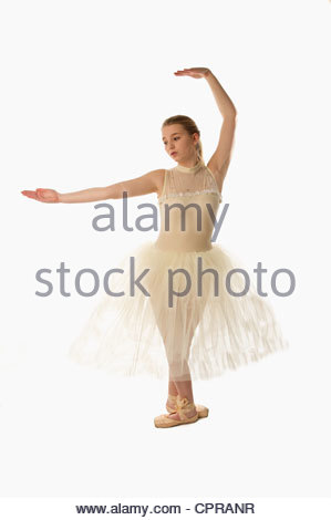 ballet dancer sitting in a tutu tying her shoe on a white background - Stock Photo