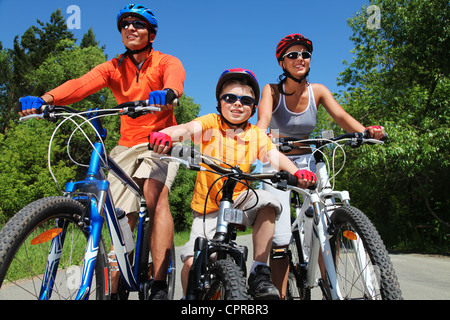 Portrait of happy family on bicycles in the park - Stock Photo