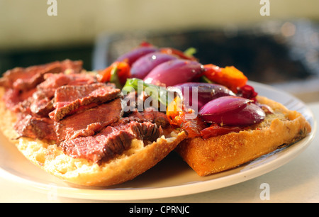 A barbequed steak sandwich filled with colorful vegetables sitting on top of a white plate in the sunshine. - Stock Photo