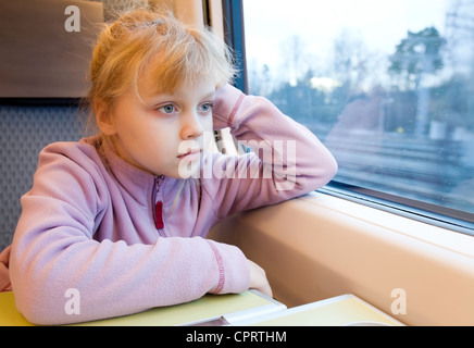 Little girl as a passenger of high speed train are looking in the window - Stock Photo