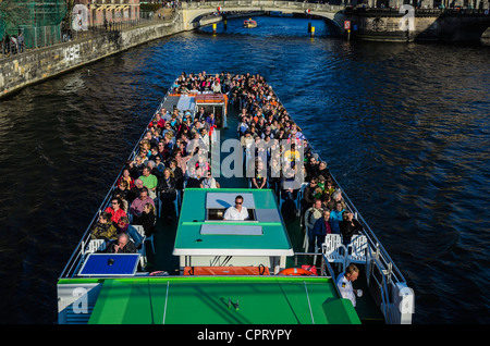 People sitting on upper deck of a cruise on the Spree River seen from a bridge - Stock Photo