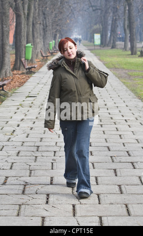 Redheaded girl walking alone in an autumn park. - Stock Photo