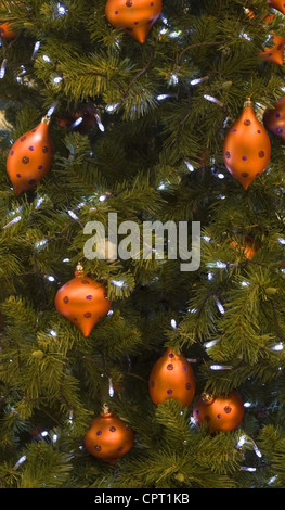 closeup image of a christmas tree decorated with orange balls stock photo