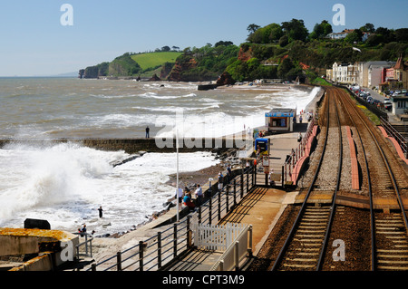Looking west from Dawlish Railway Station at the rough waves crashing along the sea wall - Stock Photo