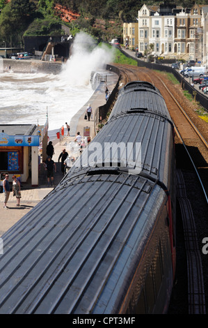High speed express train on the Dawlish sea wall as waves splash over the track - Stock Photo