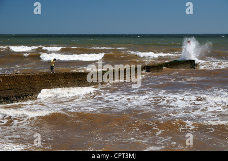 Teenage boy fishing on a wave lashed jetty at Dawlish in Devon - Stock Photo