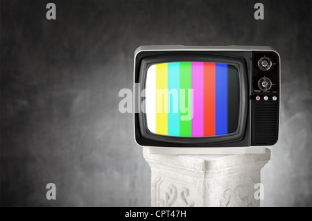 Old television with color bars on a plaster column. - Stock Photo