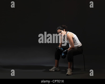 Portrait of female boxer sitting against black background - Stock Photo