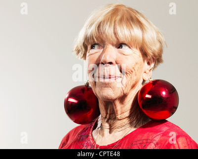 Senior Woman Wearing Red Baubles As Earrings Against White Background