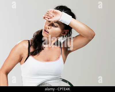 Tennis player mopping brow against white background - Stock Photo