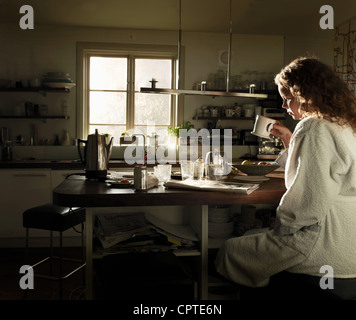 Young woman reading newspaper at kitchen table over breakfast - Stock Photo